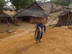 Enfant hmong jouant avec son pneu